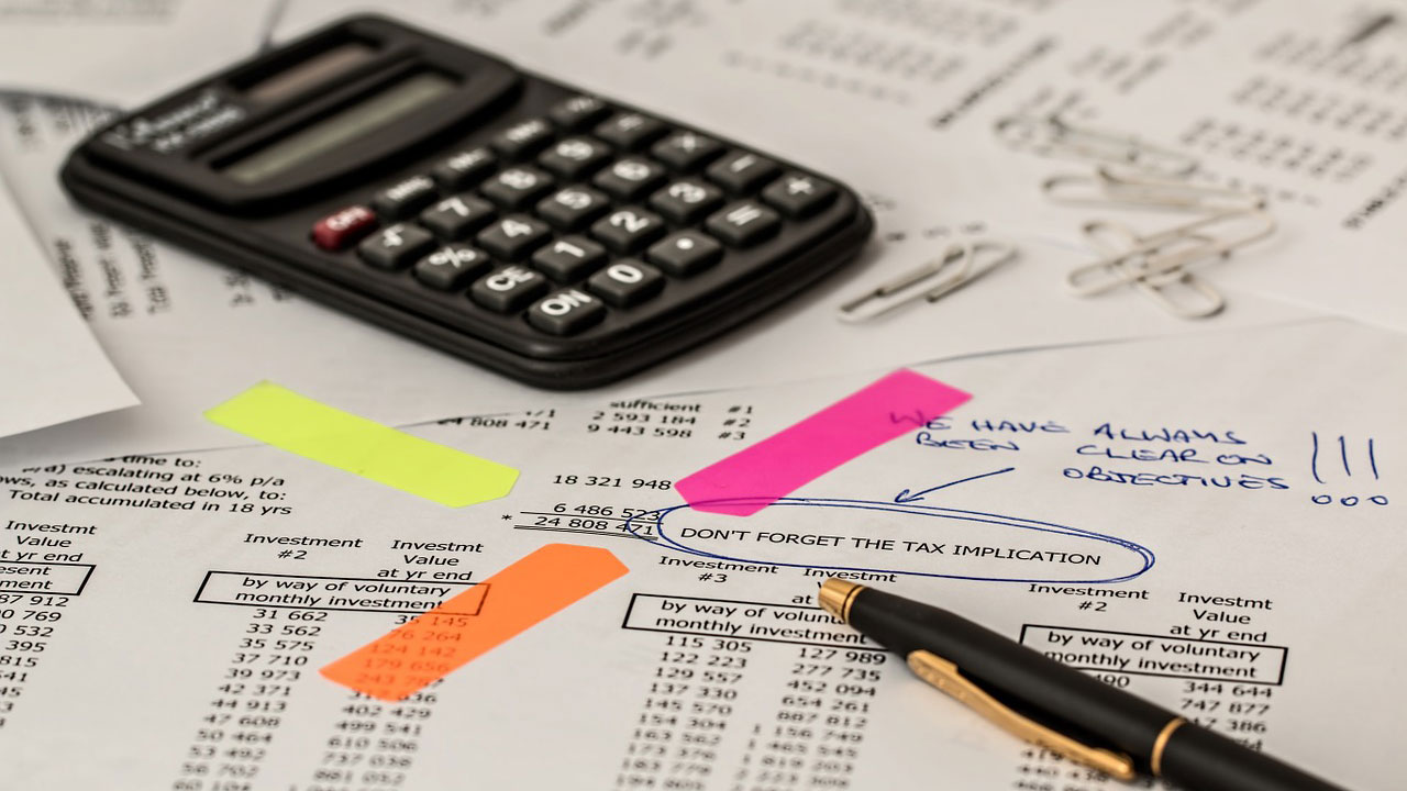 Black calculator and spreadsheets on accountant's desk