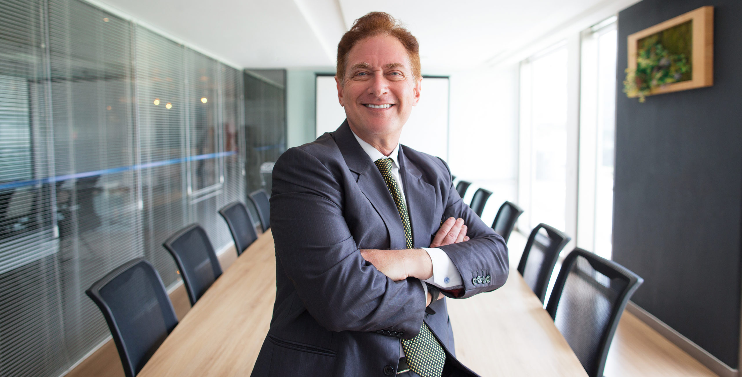 Proud middle-aged man in a suit sitting at the head of a conference table