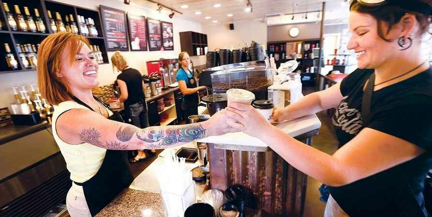 A barista with visible tattoos serving coffee to a customer
