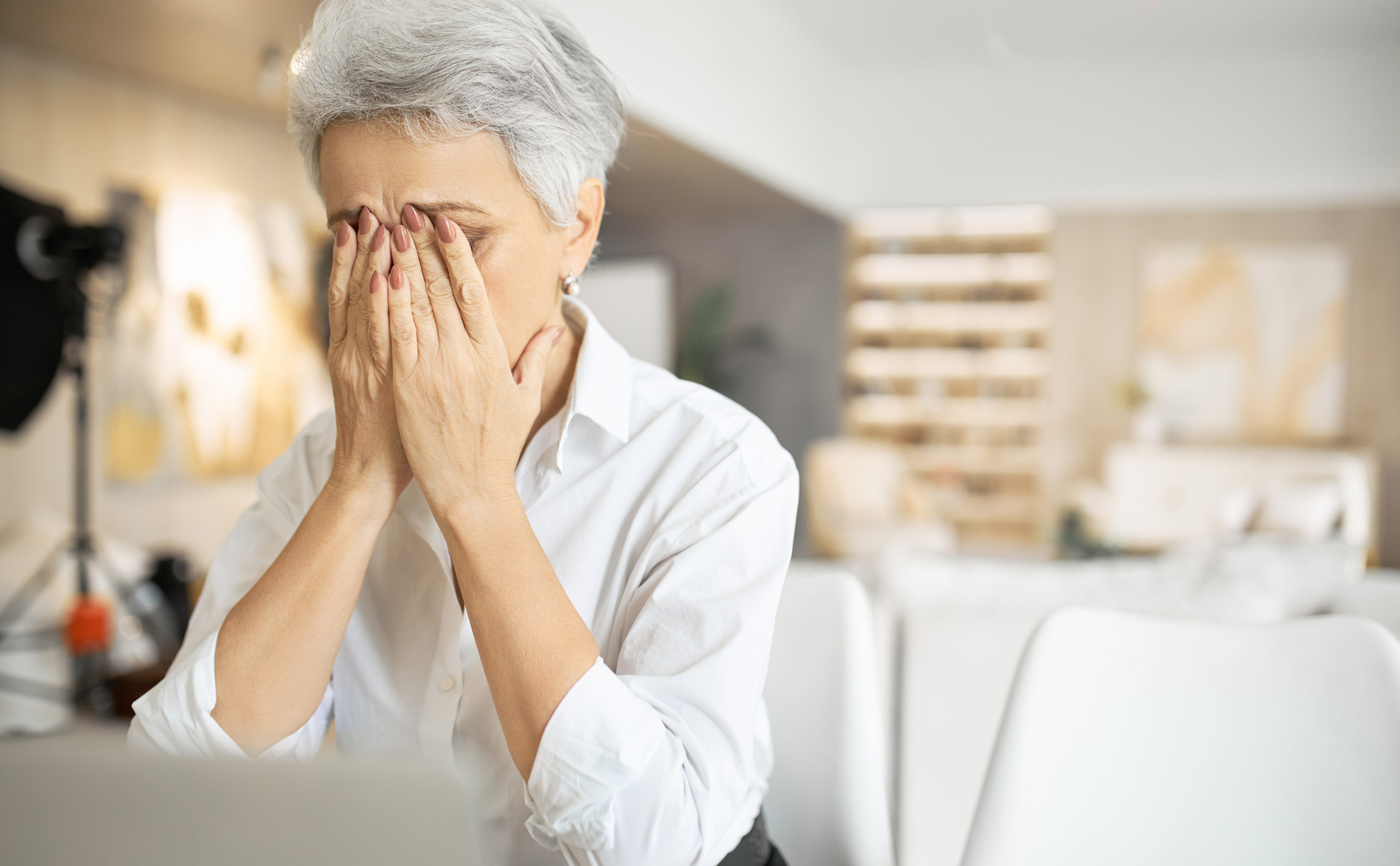 mature women sitting at a laptop with her head in her hands, feeling sad