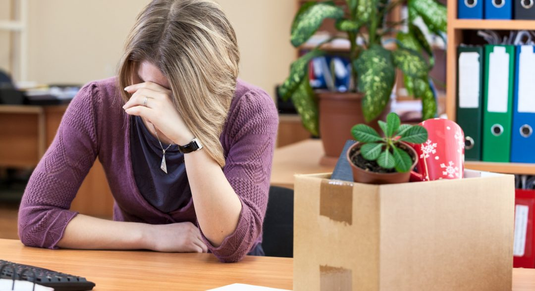 Woman sitting at her desk with her head in her hands. A cardboard box of belongs beside her.