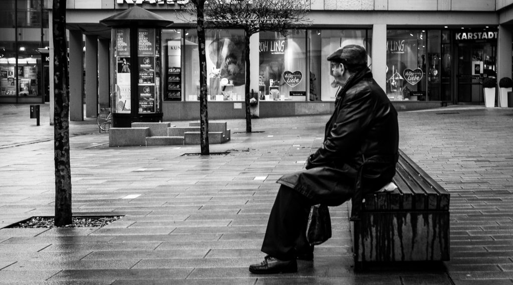 Man sitting alone on a bench in the rain