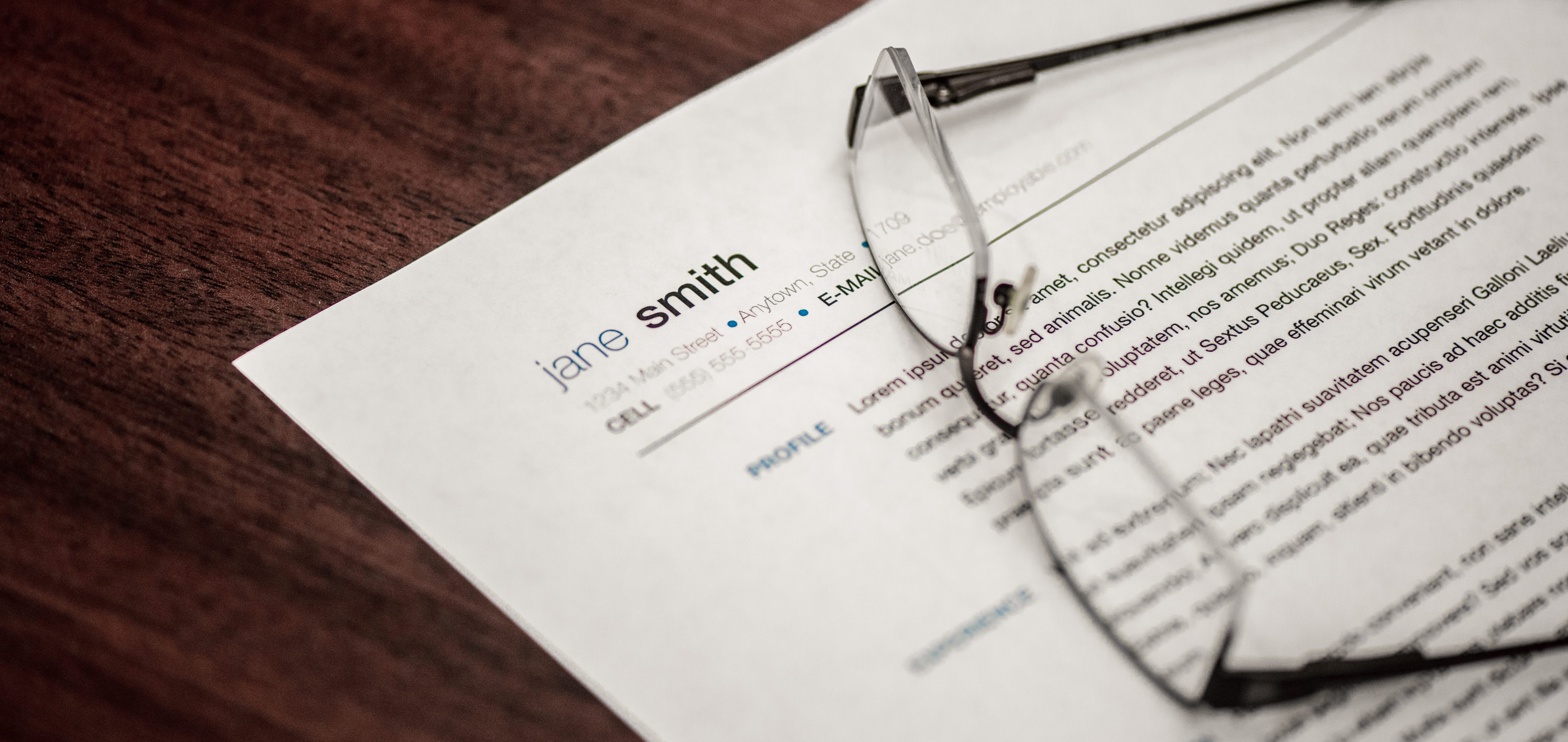 Close up of eye glasses atop a resume