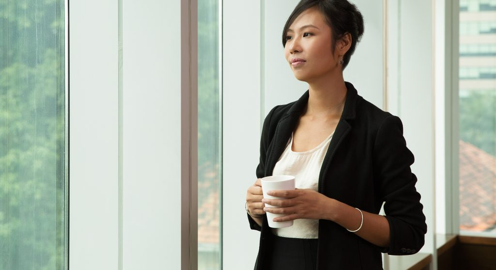 Portrait of pensive Asian businesswoman wearing costume standing in office holding coffee cup and looking out window