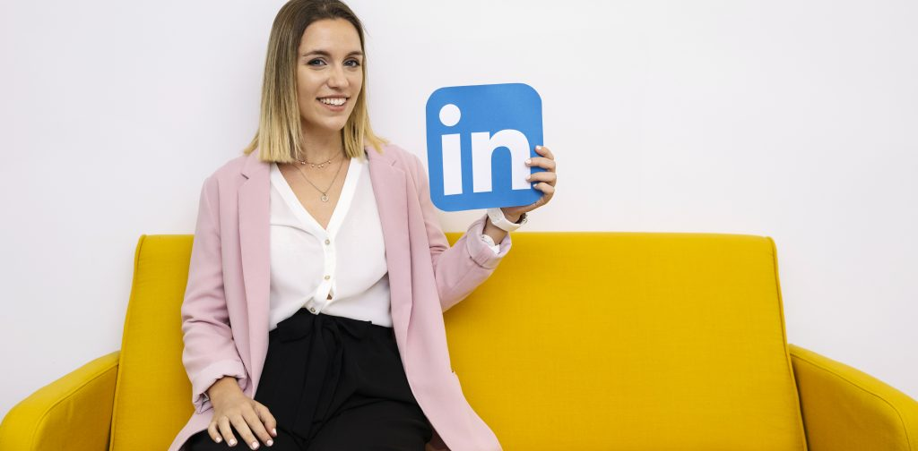 Attractive-young-woman-sitting-on-sofa-holding-linkedin-icon