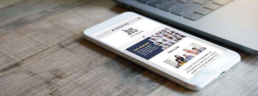 Smart phone and laptop displaying JVS Toronto's web site.