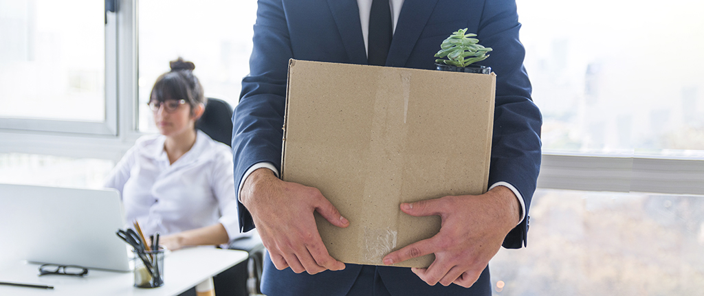 Close up of a man carrying his belongs out of the office in a cardboard box.