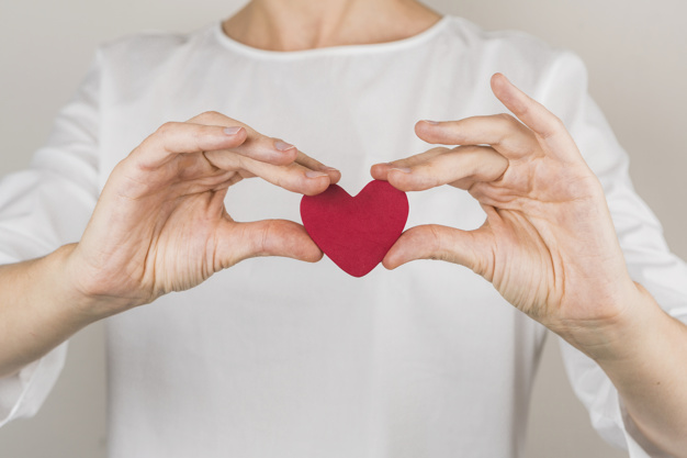 Close up of a person holding a red heart