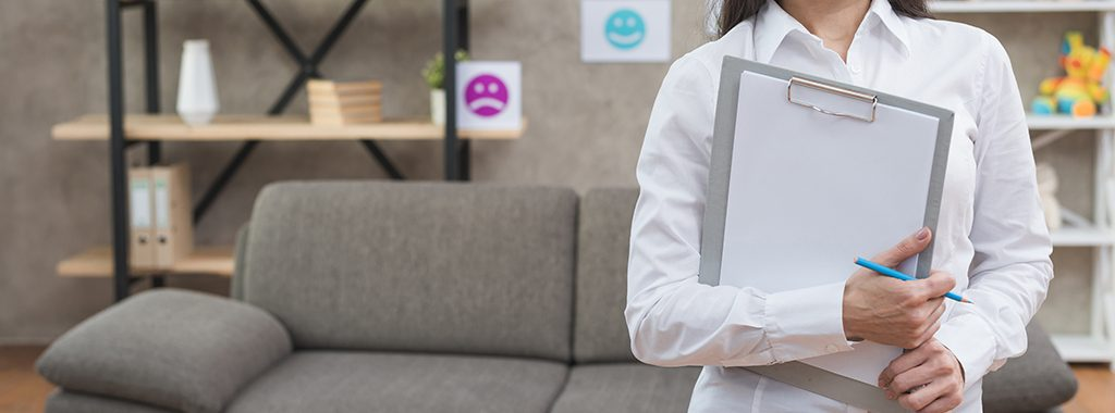 Psychologist standing in office holding clipboard and pencil.