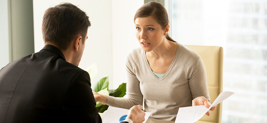 Angry businesswoman arguing with businessman about paperwork fai
