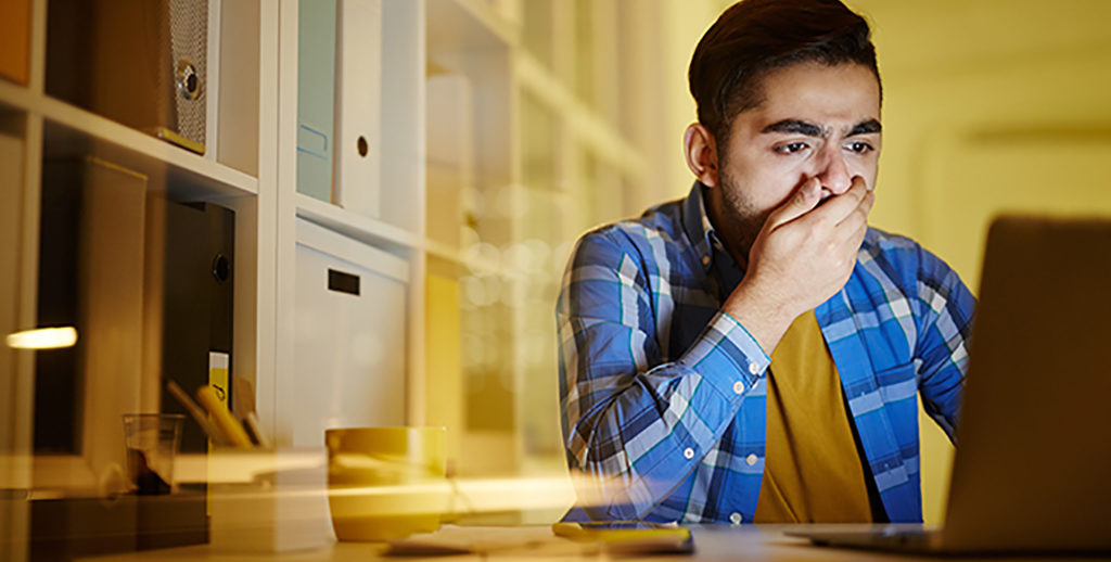 Worried guy covering mouth by hand while looking at laptop display and understanding that dangerous virus attacked his computer