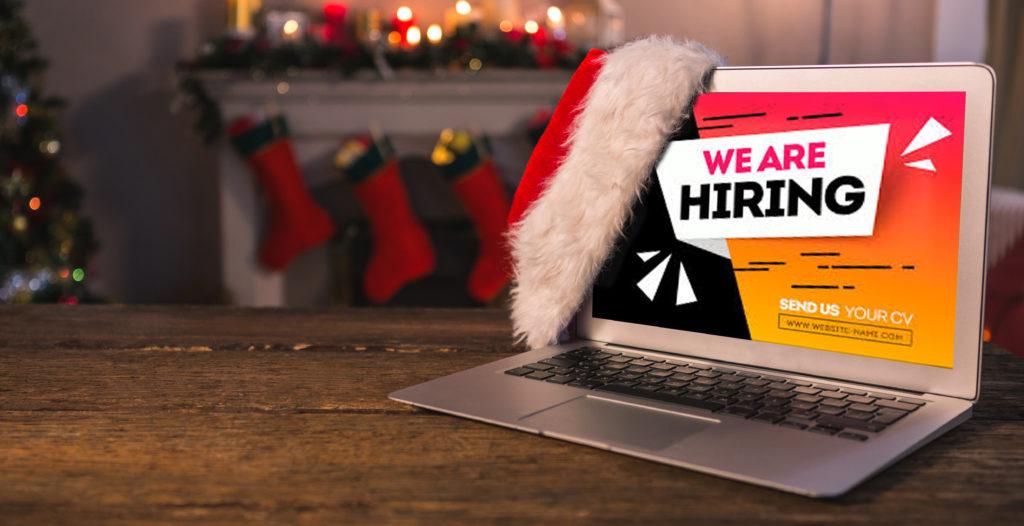 "Santa hat hanging on laptop displaying the message ""We are hiring"""