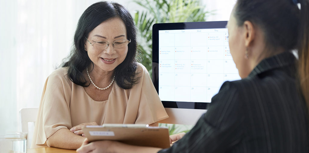 Senior Asian woman talking to insurance agent in office
