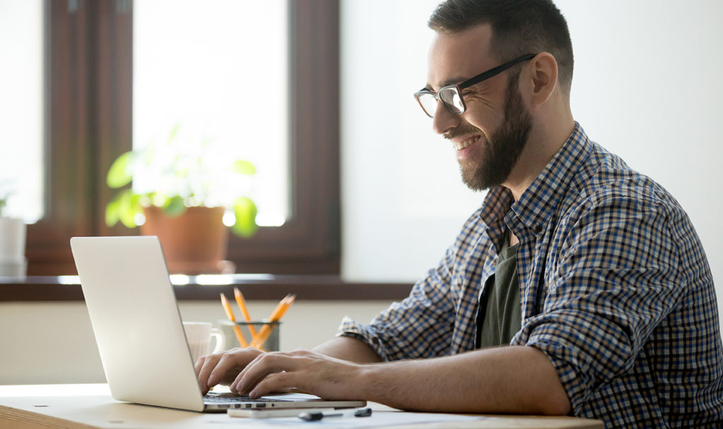 Happy male smiling at laptop, Working from home