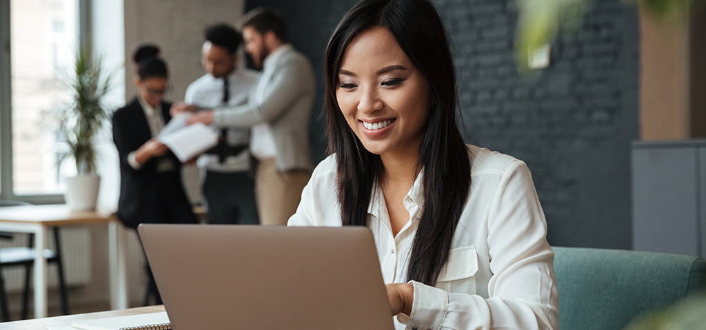 Picture of cheerful young asian business woman sitting indoors using laptop computer. Looking aside.
