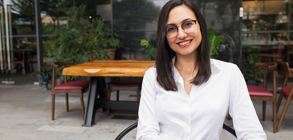 Portrait of happy female student in glasses sitting in cafe. Young Caucasian businesswoman sitting at table and smiling.