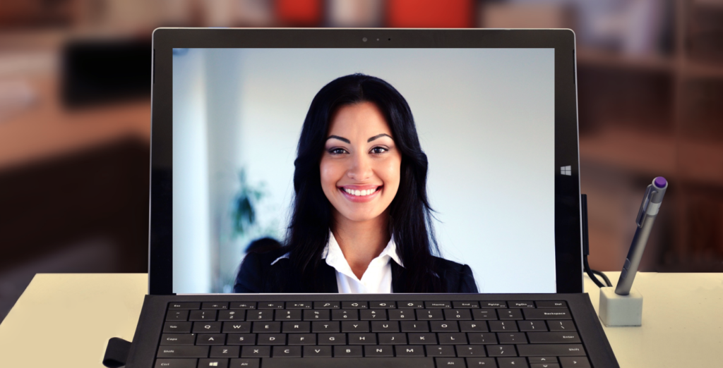 A woman appearing on a laptop top screen in a video
