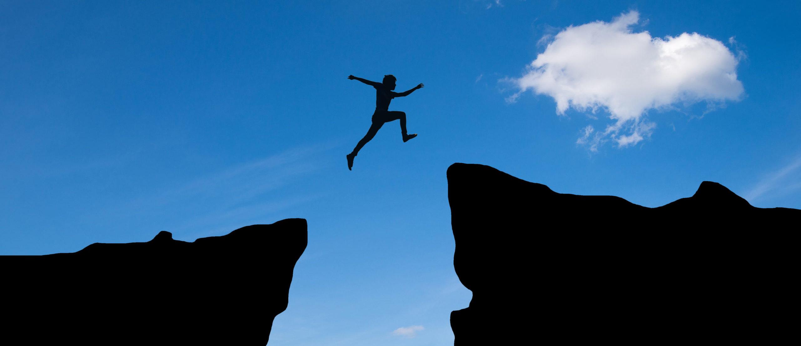 Man jump through the gap between hills