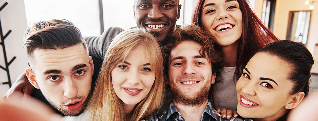 Teens having fun at restaurant. Three boys and three girls taking group selfie and laughing.