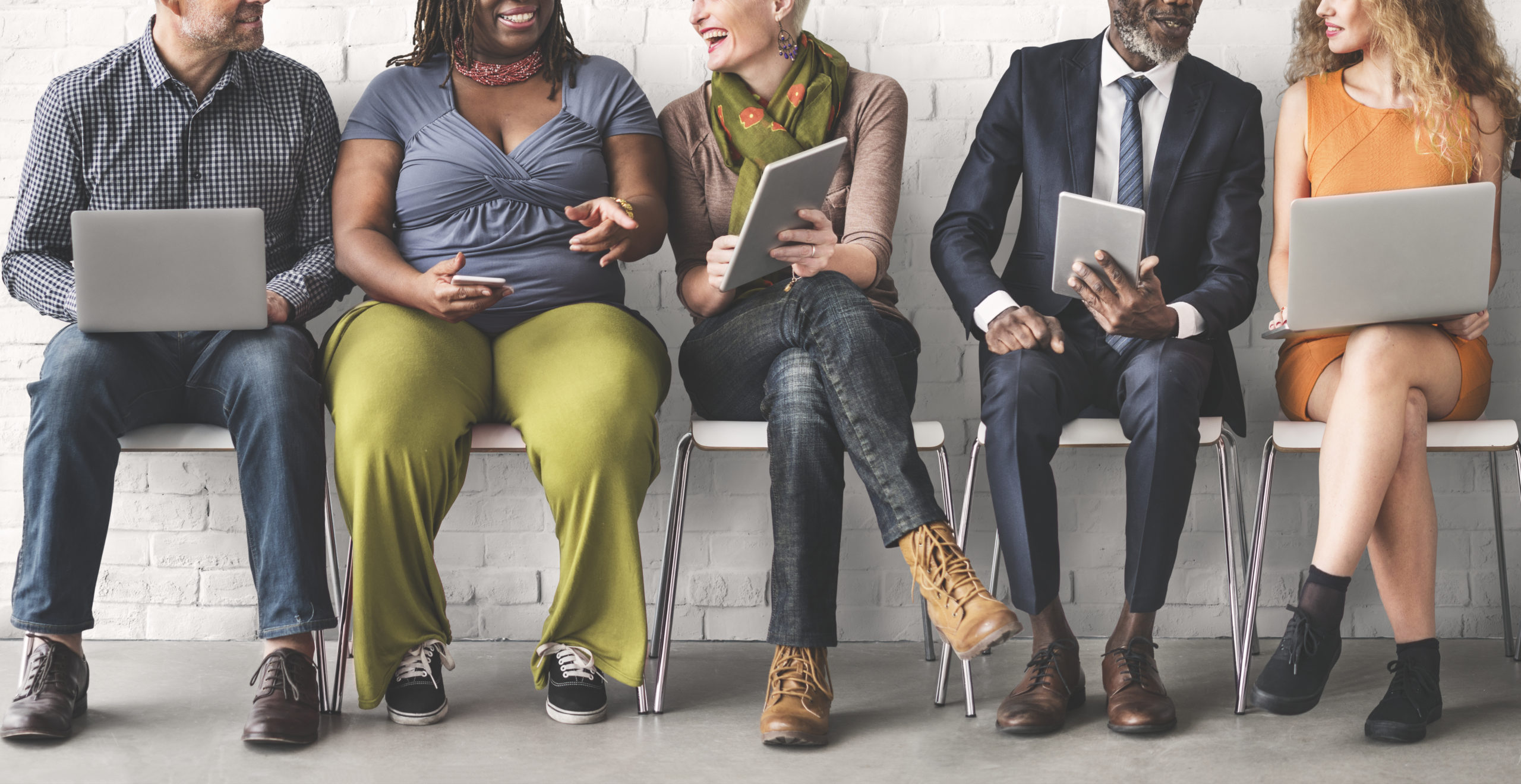 A group of diverse people using digital devices and talking together
