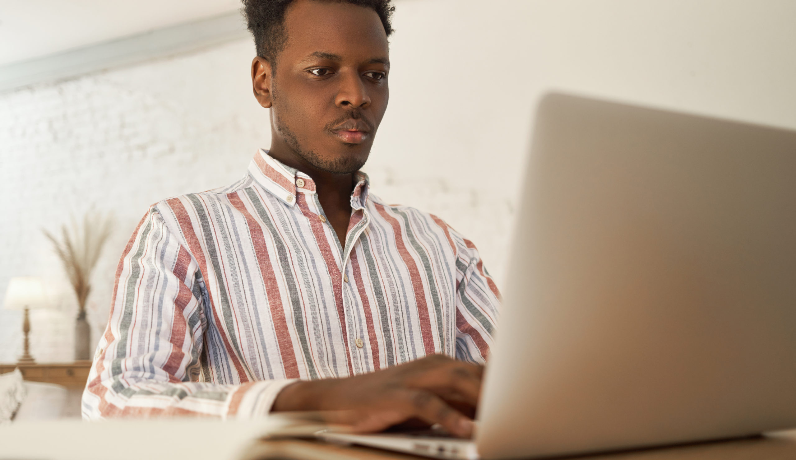 Focused young african male applying for jobs online